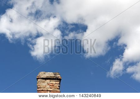 Old Brick Chimnet Against Blue Sky With Clouds.