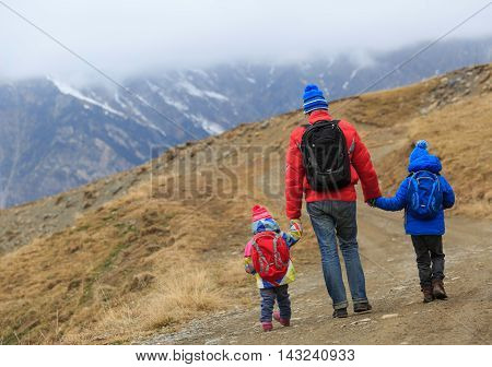 father with little son and daughter hiking in winter mountains
