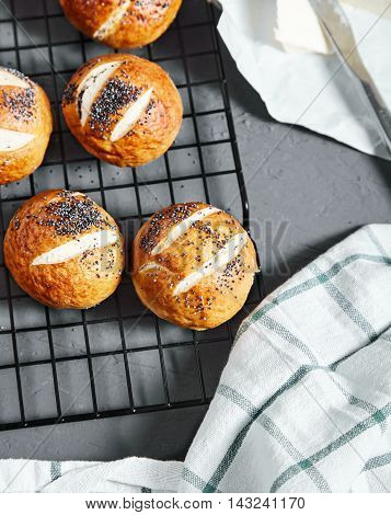 Top view of homemade baked golden pretzel buns with poppy seeds with buuter near it on stone background. Pretzel bun is german cuisine dish, ideal for lunch or breakfest with butter and tea.