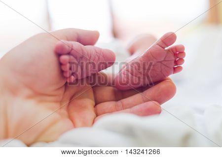 Loving Mother Holding Her Child's Feet