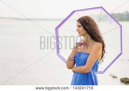 Happy Young Girl Standing With An Umbrella On A Background Of A Morning River