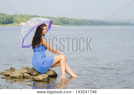 Lonely Sad Young Woman With An Umbrella Sits On A Rock By The River