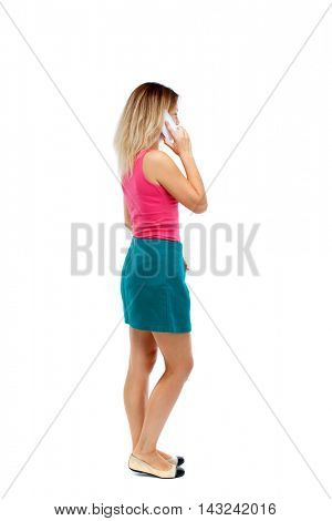 back view of a woman talking on the phone.  backside view of person.  Rear view people collection. Isolated over white background. Blonde in a red sweater and green skirt standing cancer and talking