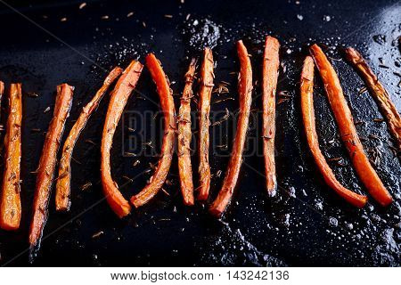 Roasted caramelized and glazed carrots with caraway on dark surface