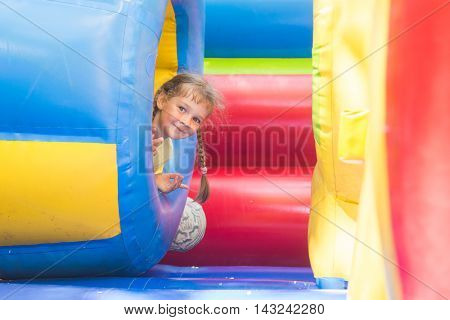 Happy Little Girl Got Out Of The Inflatable Soft Barrel While Playing On The Trampoline