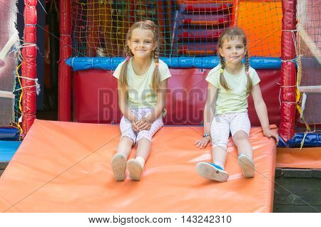 Two Girls Naprygalis Soft Children's Play Room And Sat Down To Rest