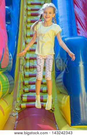 Happy girl jumping on an inflatable trampoline