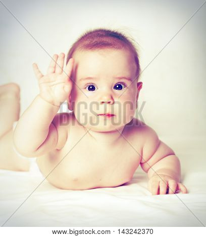 little beautiful Baby with hand up - hello!