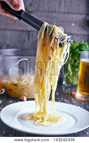 Pasta with gralic and chili. Hand with tongs move spaghetti with garlic, oil and chili to a white plate on wood background