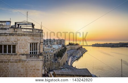 Valletta, Malta - Panoramic skyline view of sunrise in Malta with the ancient walls of Valletta and Grand Harbour