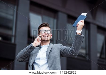 Always connected. Cheerful delighted handsome man holding purse and keeping hand up while talking on cell phone