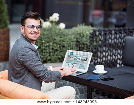 Rise your mood. Positive content smiling man sitting at the table and using laptop while resting in the cafe