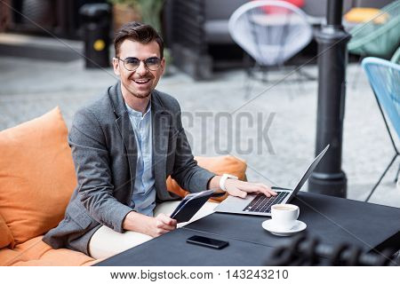 My working days. Positive content handsome man sitting at the table and using laptop while expressing joy in the cafe