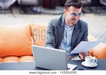 Diligent worker. Cheerful smiling businessman working with papers and using laptop while sitting in the cafe