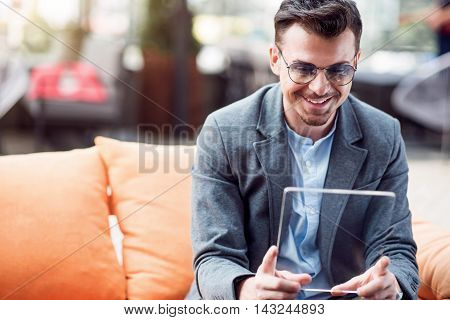 Share gladness. Joyful smiling businessman using tablet and sitting at the table while resting in the cafe