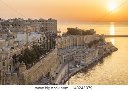 Sunrise in Malta with the ancient wall of Valletta and Grand Harbour