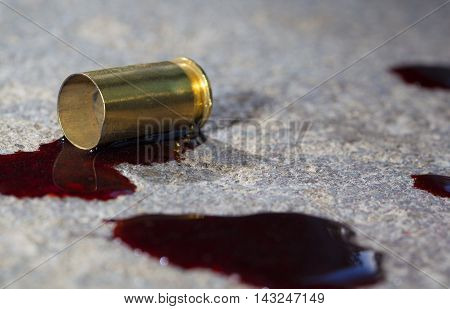 Handgun brass with some blood on the concrete