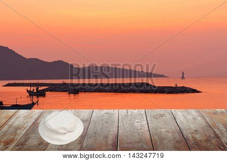 white hat on wood table in morning sunrise at sea and space for text may be used as background