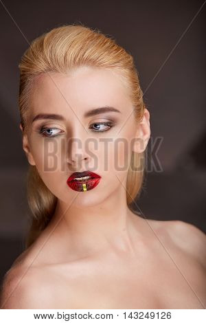 Closeup portrait of a young blonde woman bright makeup. Art visage young woman with red full lips on a black background.