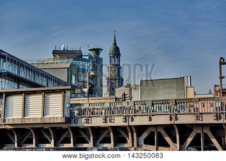HAMBURG, GERMANY - MARCH 26, 2016: View at elevated railway station, Gruner and Jahr headquarter building and the tower of the famous Michel in Hamburg.