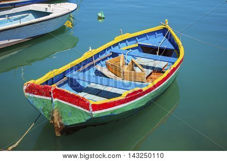 Malta - Colorful Mediterranean traditional Luzzu fishing boat at Marsaxlokk on a sunny summer day with green sea