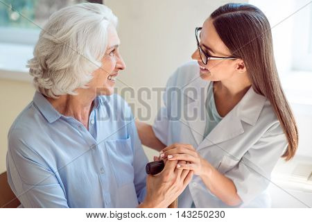 With you. Close up of smiling nurse embracing delighted senior woman