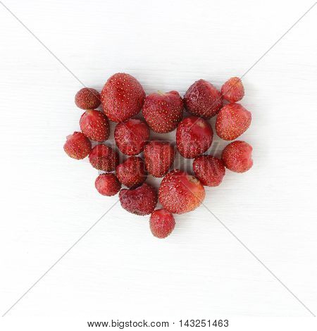 background with heart symbol of strawberries on a light wooden background top view / strawberry heart
