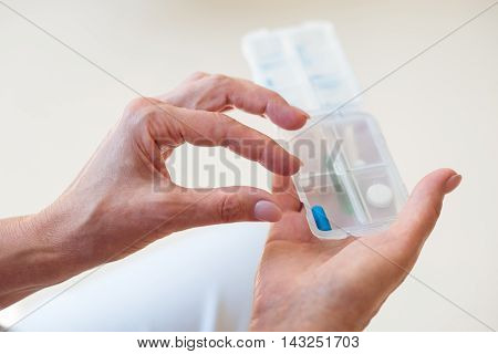 Health. Close up of female hands holding little box with different pills