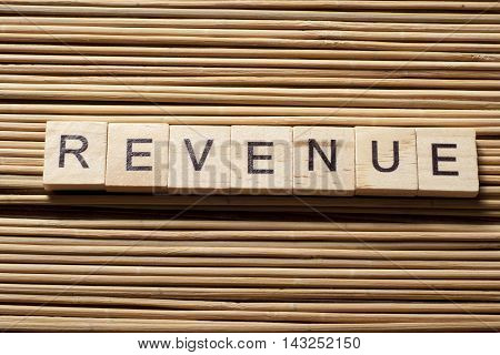 REVENUE word written on wood block at wooden background