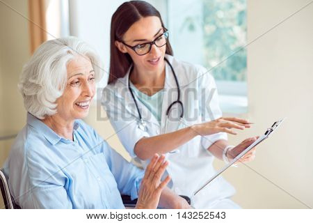 Professional one. Delighted senior woman and female positive and kind doctor holding clipboard and pen at hospital ward