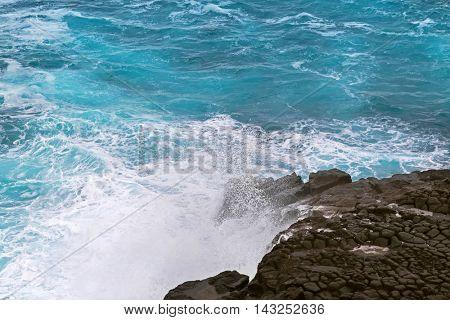 Deep blue sea water splashing volcanic rock at blowholes, rock tunnels, at Cape Bridgewater in Victoria, Australia