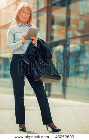 Mature businesswoman working on a digital tablet.Businesswoman standing in front of an office building.