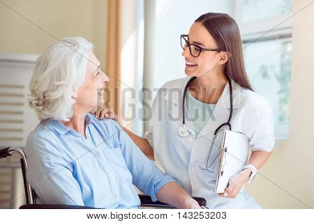 Live long. Cheerful senior woman and positive doctor holding clipboard while at hospital ward