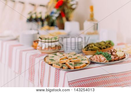 Close up of different salty snacks and pickles in ethnic pottery on catering table at banquet hall.
