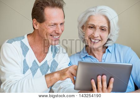 Modern. Happy senior mom and son using tablet pc computer