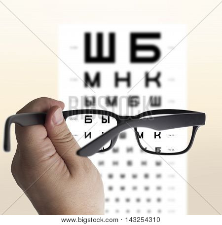 Eyeglasses in hand for eyesight Russian/Cyrillic test chart background isolated