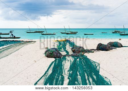 large fishing nets lying on african beach with boats near the shore on the background