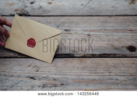 Man Hand With Wax Seal Envelope On Wooden Background