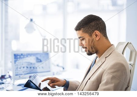 Cropped shot of a young businessman.Businessman working on his digital tablet in the office.