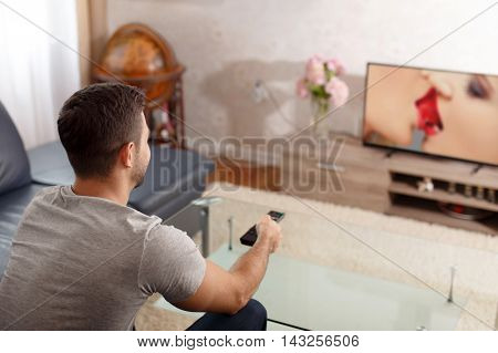 Man watching sex movie in TV on adult channel