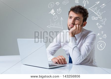 young man thinking uses a laptop computer while sitting at a table. Office clothing