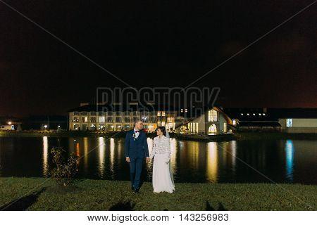 Romantic newlyweds posing near night lake illuminated with bright light from banquet hall windows.