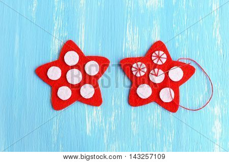 Sewing red Christmas star. How to sew on a white felt balls to a red felt stars. Decorative stitch. Christmas crafts idea for kids and beginners. Step. Manual. Top view. Closeup
