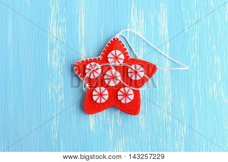 Join the felt edges of Christmas star with white thread using a decorative blanket stitch. Two felt details of Christmas star on a blue background. Winter crafts instruction for kids. Step. Closeup