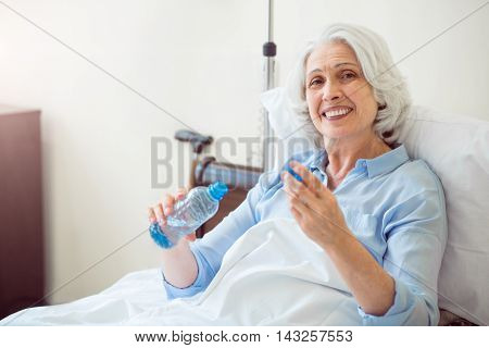 Positive granny. Smiling and merry old woman lying in bed and holding bottle of water
