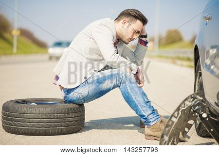 A young man with a silver car that broke down on the road.He is sitting near car with punctured tire.