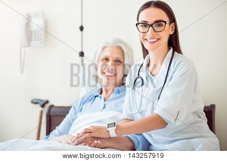 Just trust. Positive old woman lying in bed and young merry doctor holding her hands