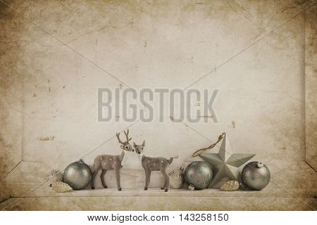 Reindeer on old wooden christmas background for a greeting card in brown and silver with balls
