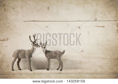 Reindeer on old wooden christmas background for a greeting card.