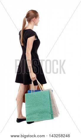 back view of woman with shopping bags. backside view of person.  Rear view people collection. Isolated over white background. Blonde in a short black dress holding paper bags.